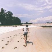 Young Man running along beach