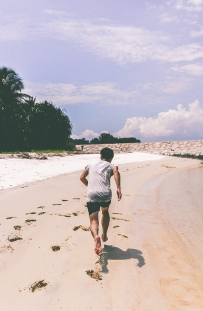Young Man running along beach