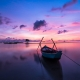 thin rowboat on river during purple sunset